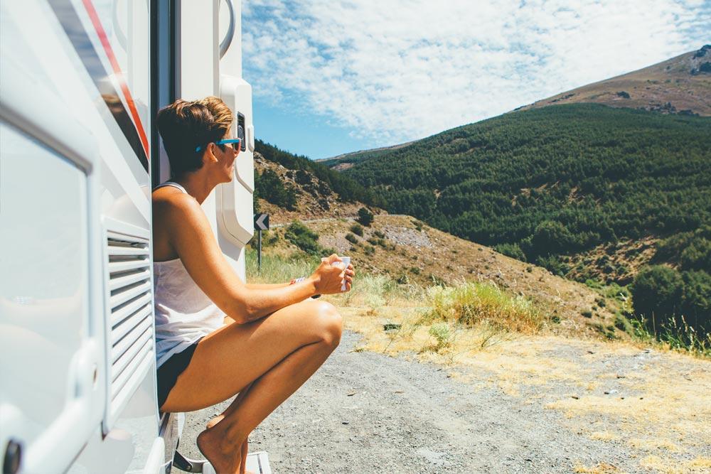 Mujer haciendo una pausa durante su viaje en autocaravana