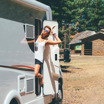 Mujer disfrutando de los cálidos rayos de sol desde la puerta de su autocaravana. La ruta ha sido programada con la información para planificar tu viaje en Autocaravana