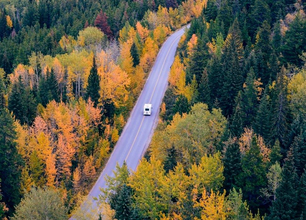 Familia circulando por uno de los destinos ideales para viajar en autocaravana: los bosques y zonas de montaña.